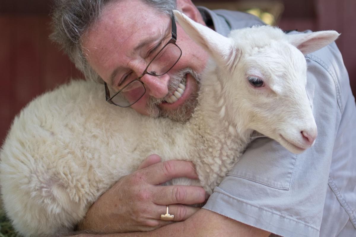 man hugging goat