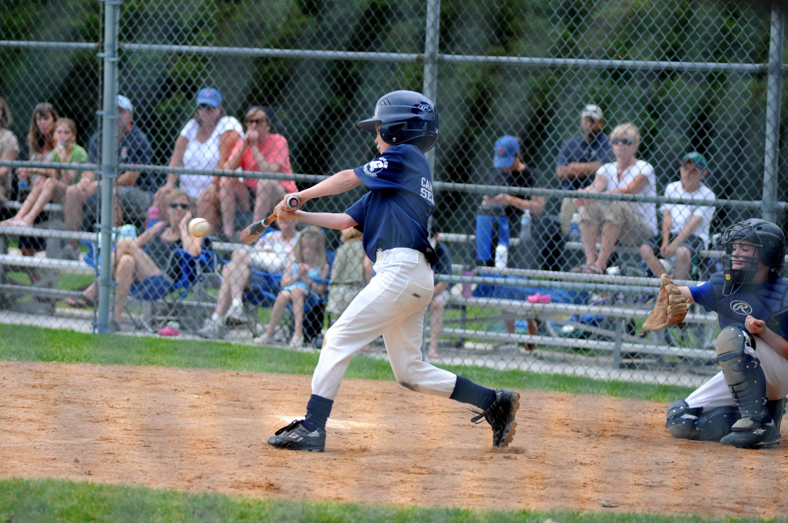 kid hitting baseball at little league game