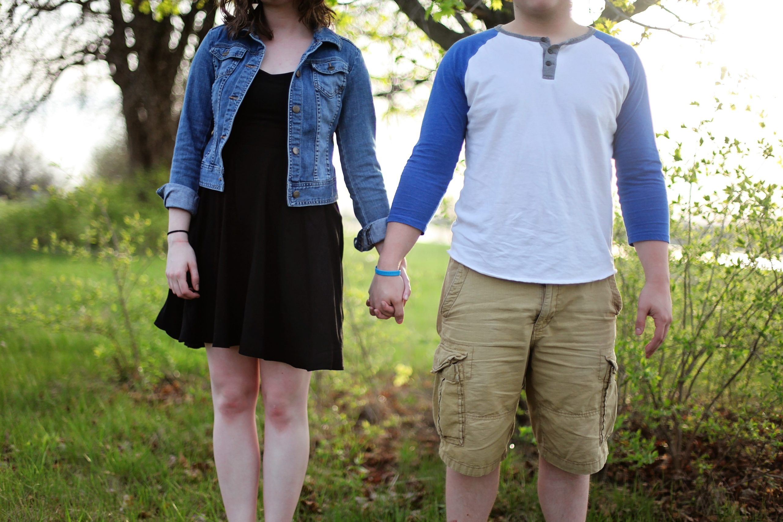 Couple holding hands in grassy field