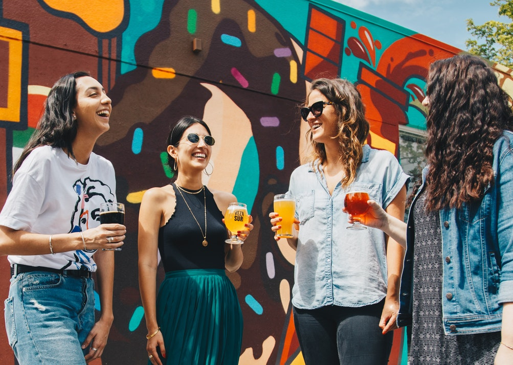 Four women drinking beer outside of a brewery