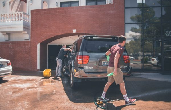 Two men washing a gray car