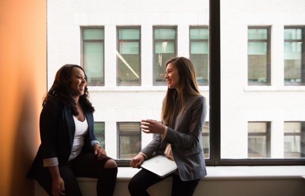 Two women in an office building talking together