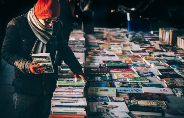 A man browses through books on a table outside