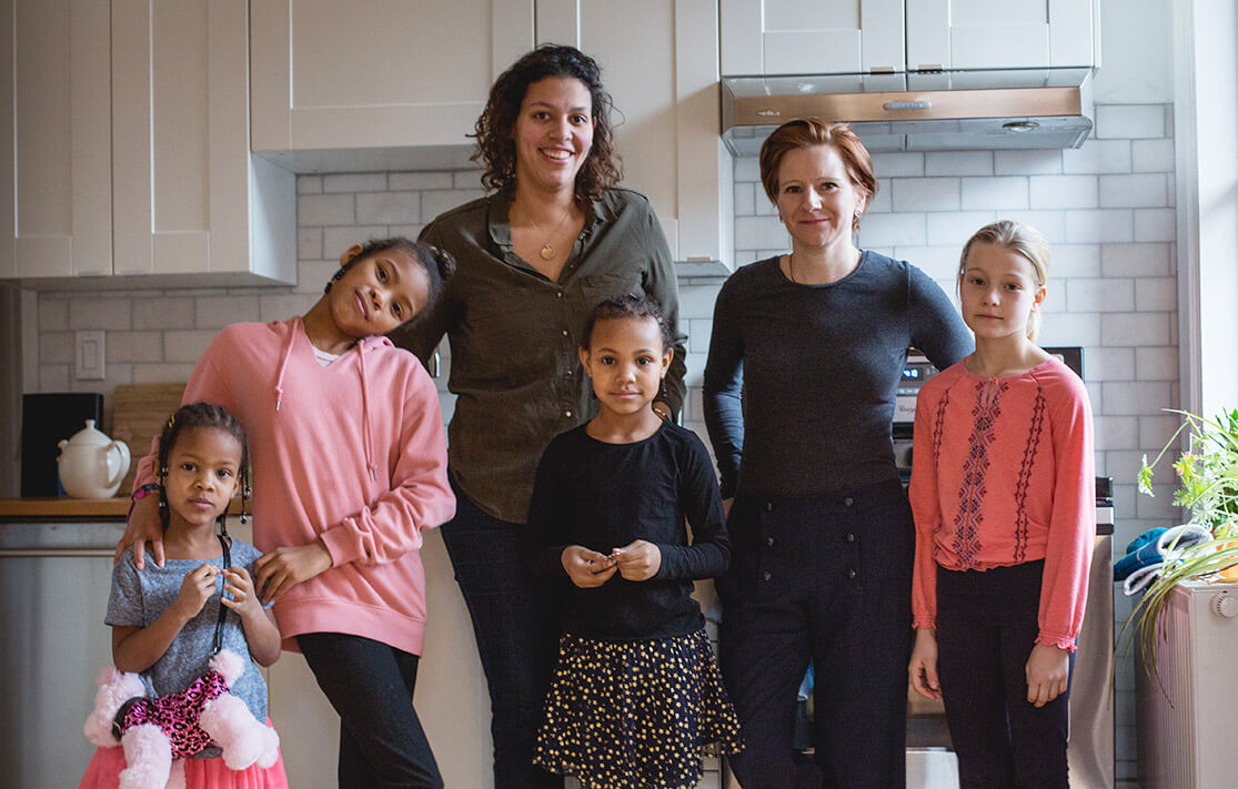 family with four children standing in their kitchen
