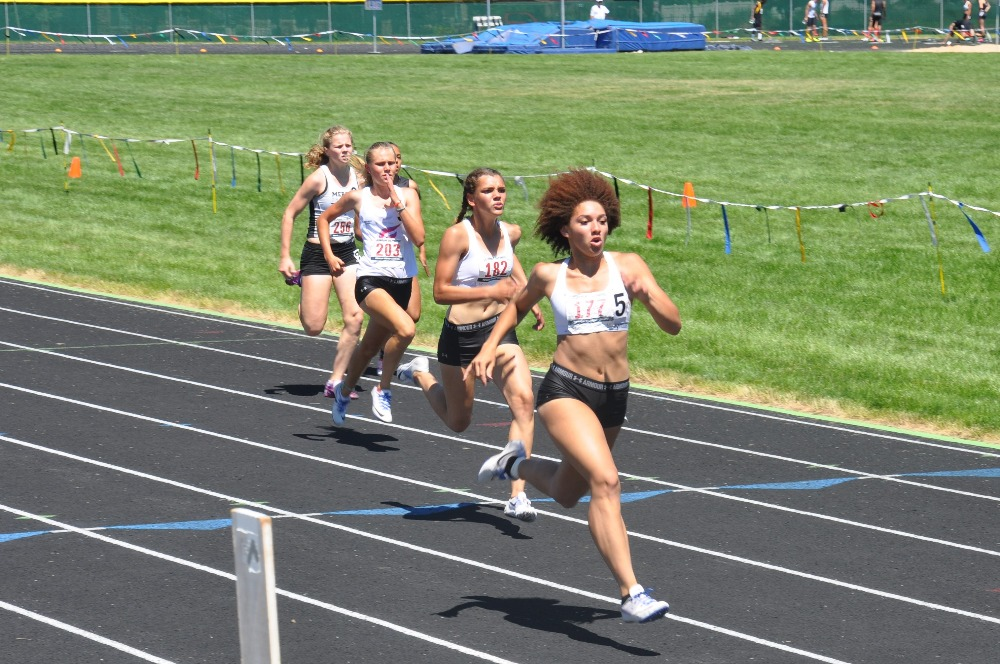 four women running on a track for a competition