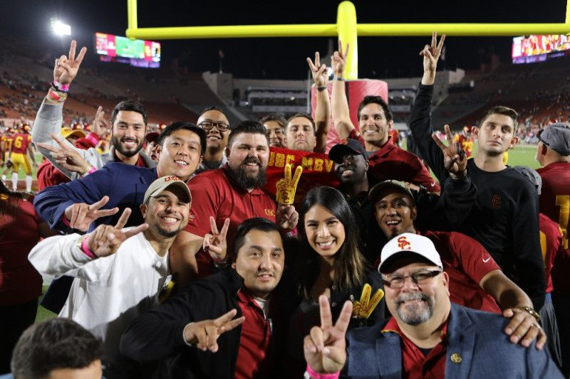 group of people smiling and holding up peace signs for the camera at a football game