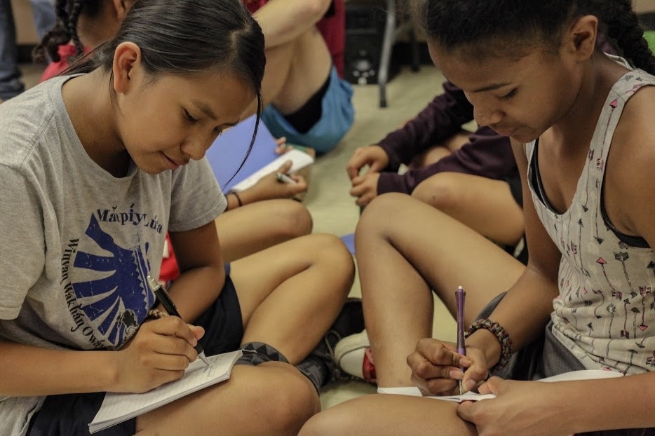 two young girls sitting down writing on notepads with pens