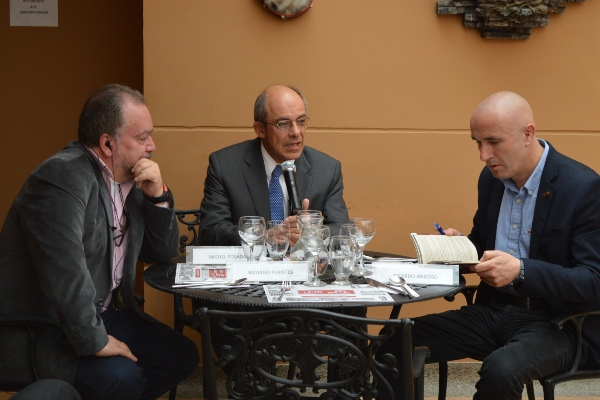 three men in suits sitting at a table talking