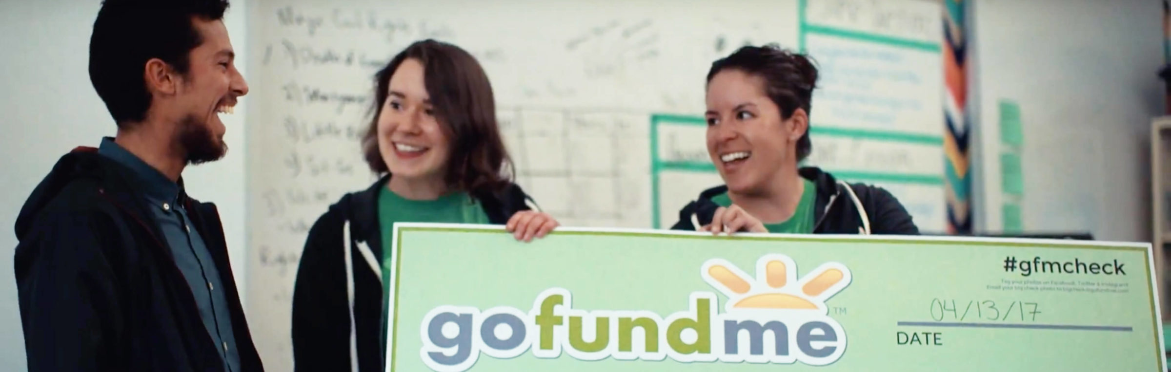 Two GoFundMe employees present a check for $1,000 to a teacher