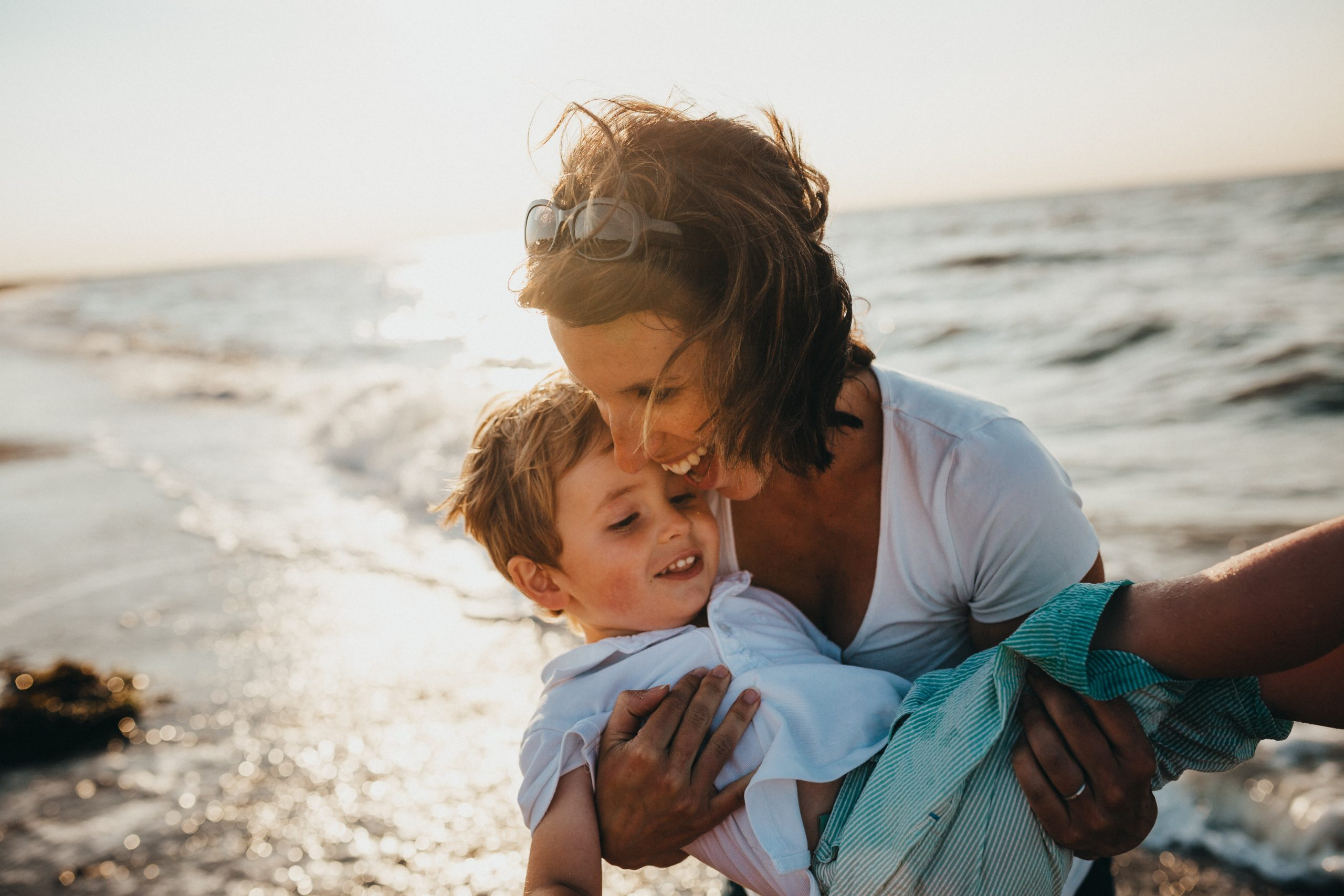 A woman holding a toddler on the beach while smiling