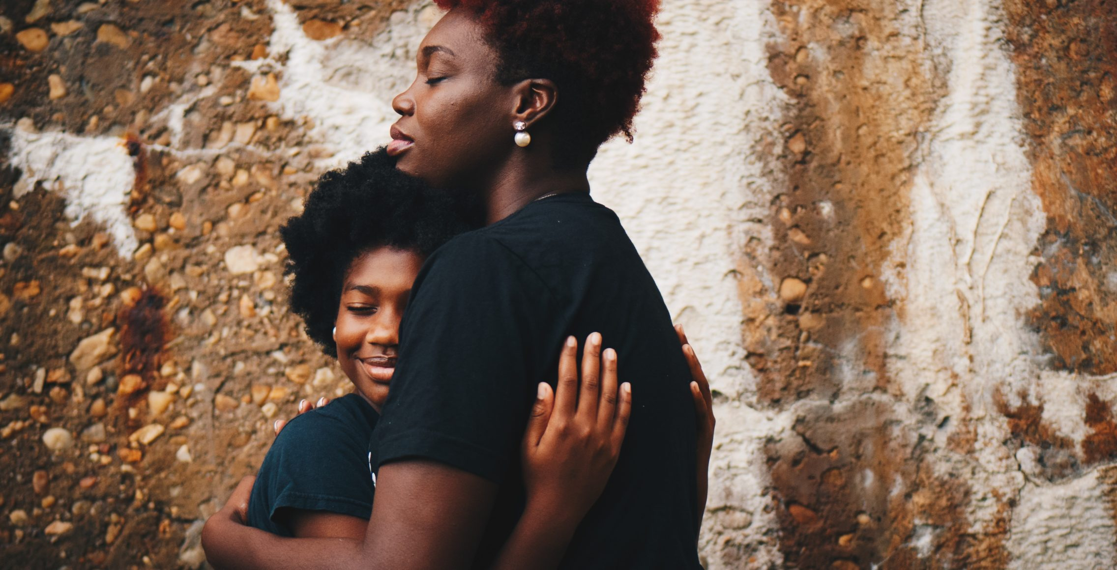 Two women in black shirts hugging