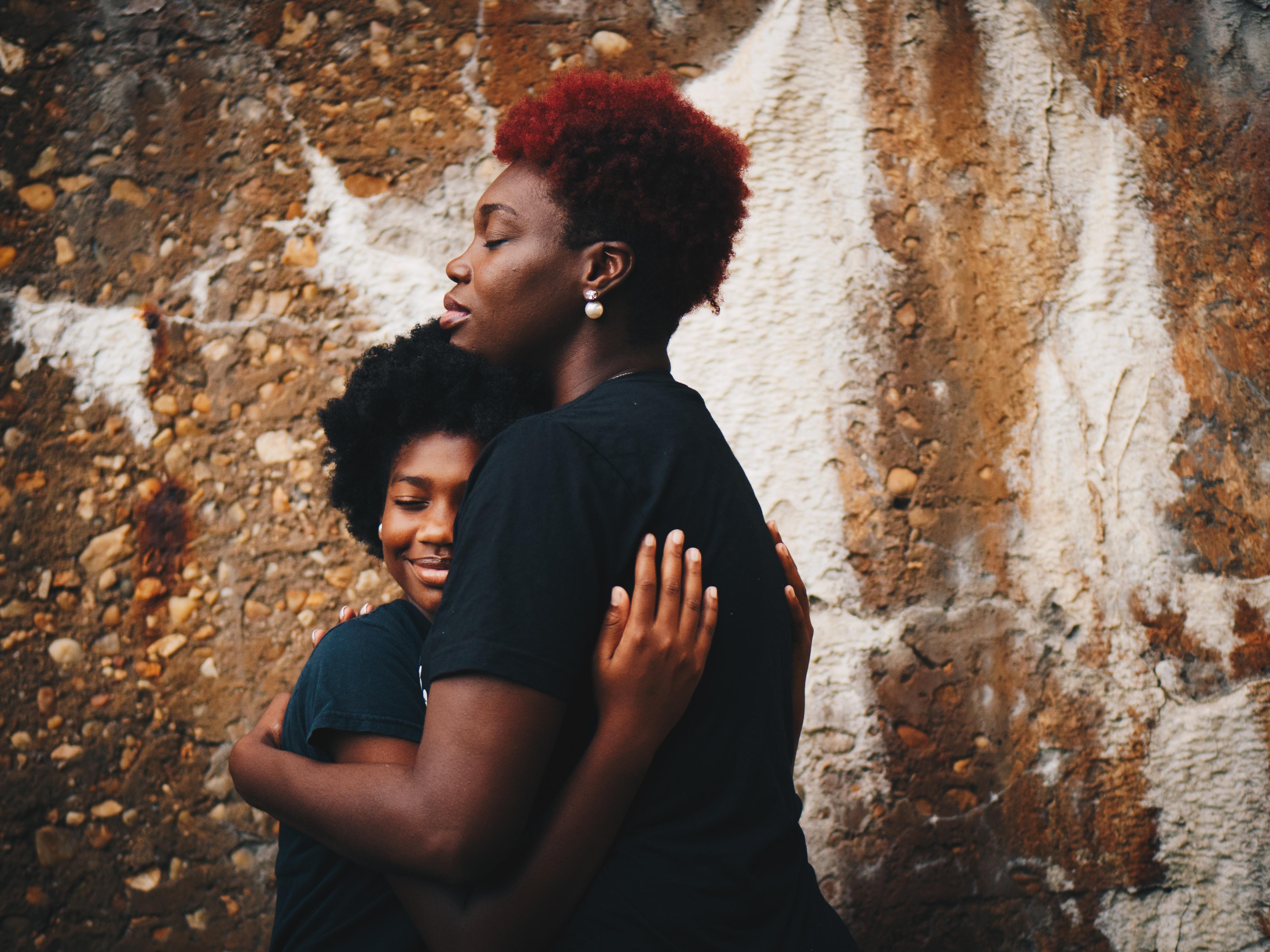 Two women in black shirts hugging