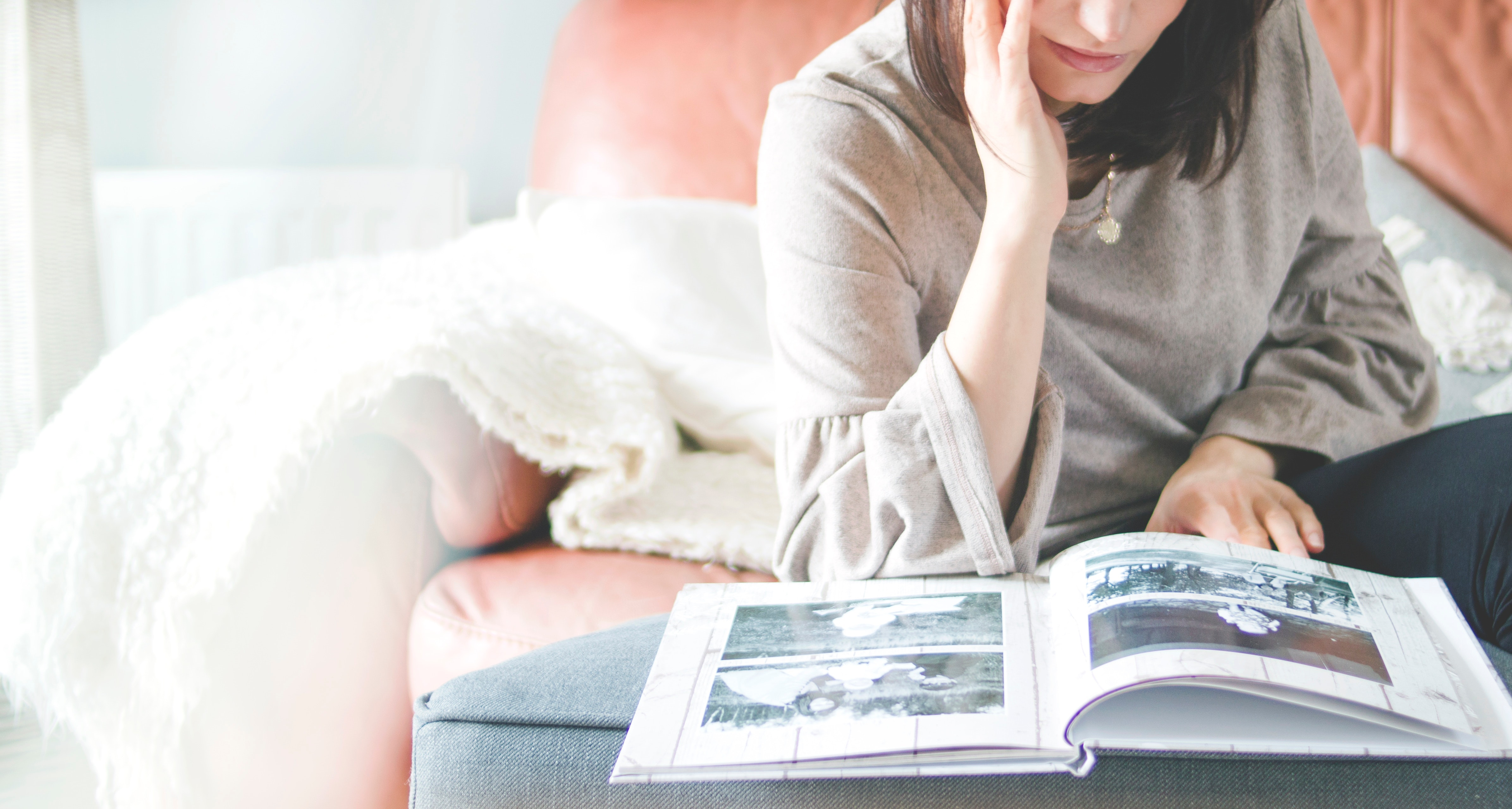 Woman sitting on a couch looking at a photo album