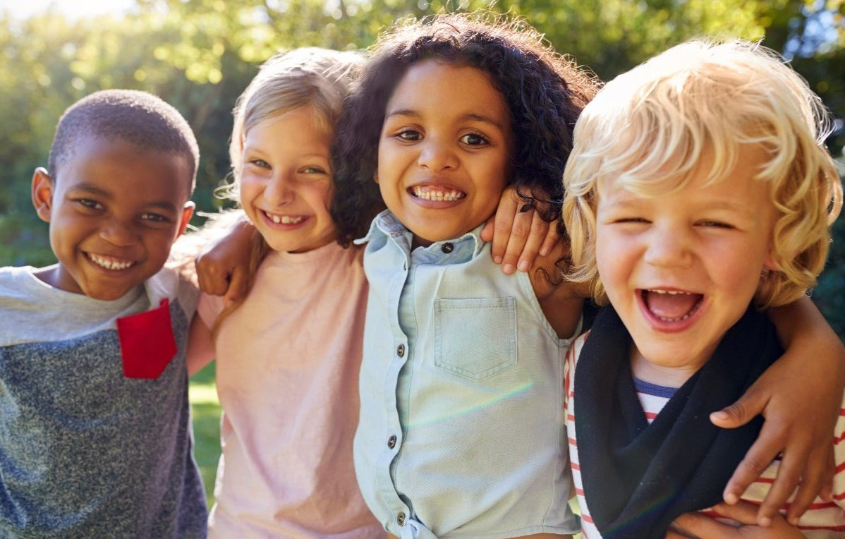 group of four young kids smiling