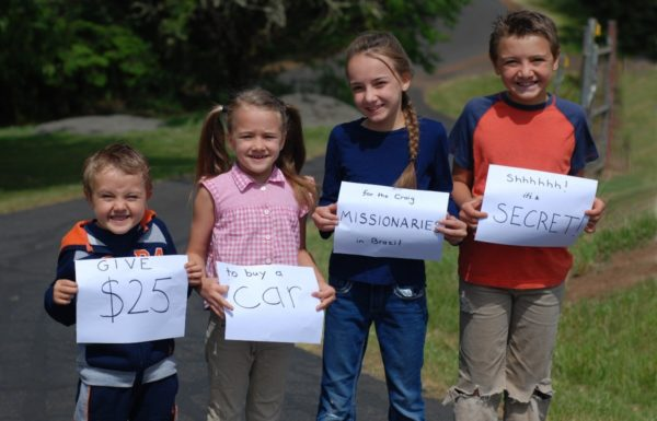 four kids holding up signs for charity car wash
