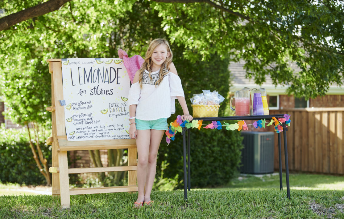 young girl standing in front of her charity lemonade stand