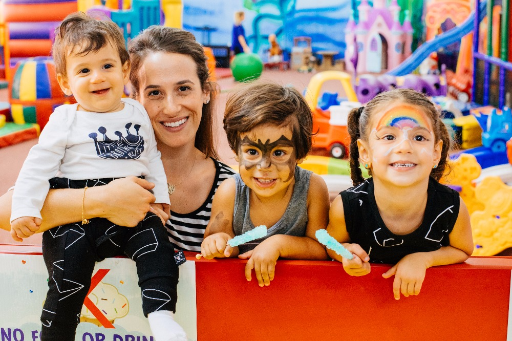 mom and her three kids in face paint at a fair