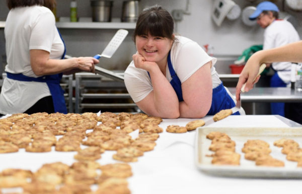 young woman poses behind rows of cookies in an industrial kitchen