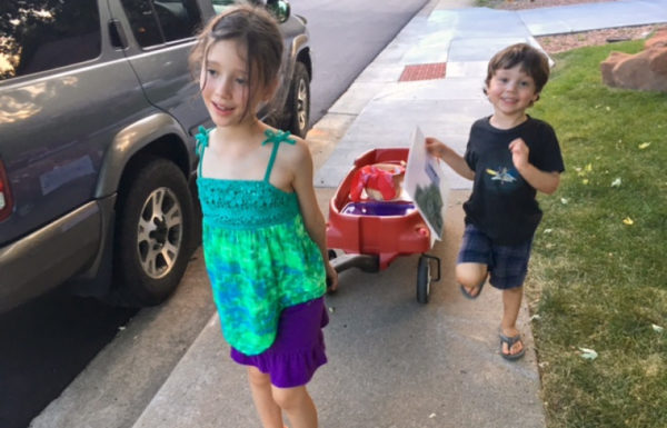 Two children pull a wagon down the sidewalk