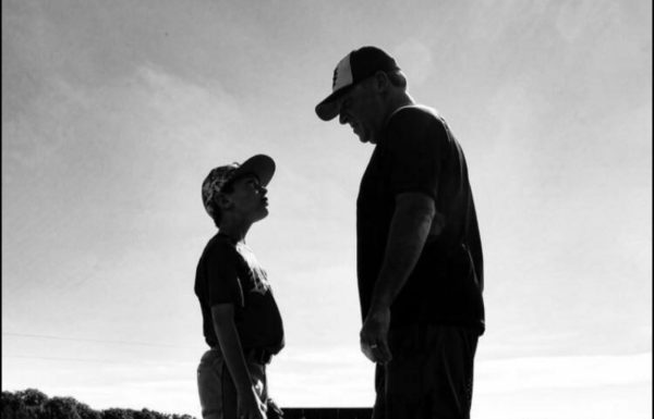 Black and white image of a man and boy staring at each other in silhouette outdoors