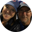 Man and woman in baseball caps smiling