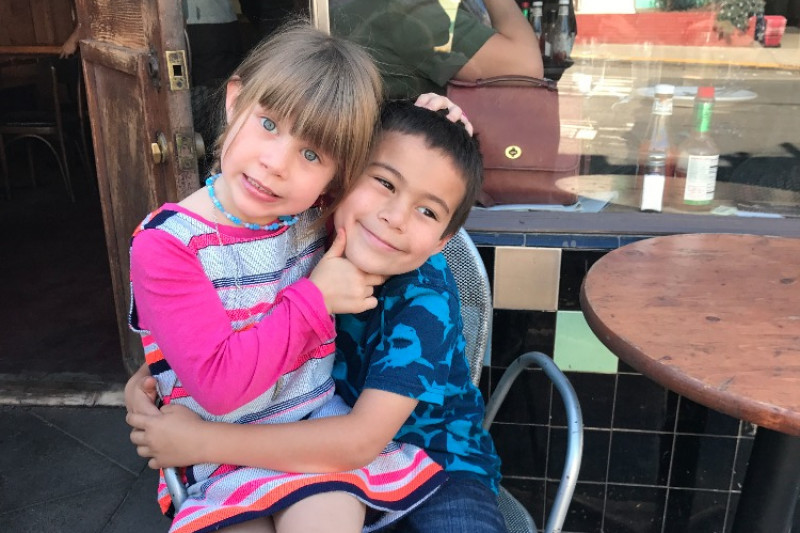Two kids sharing a chair, sitting outside of a cafe, and smiling and embracing each other