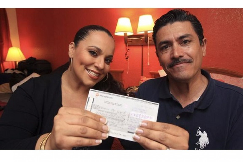 Man and woman in a hotel room holding a check together