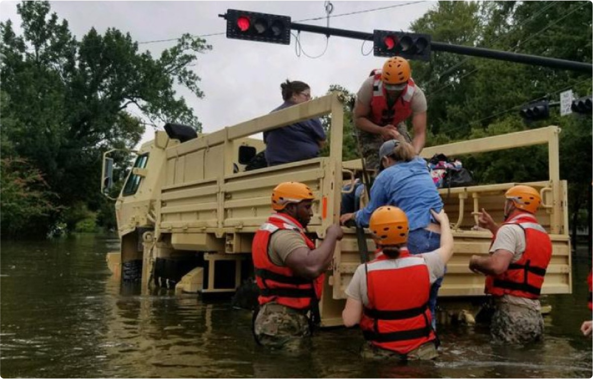 Rescue workings help woman into the back of a rescue truck during a flood