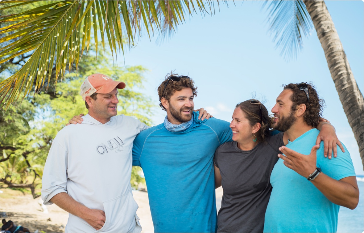 Group of four middle-aged friends with their arms around each other on a beach
