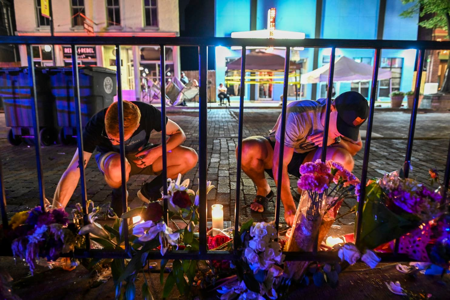 Two young men placing flowers and candles against a fence in a city street during a vigil for the Dayton, Ohio shooting
