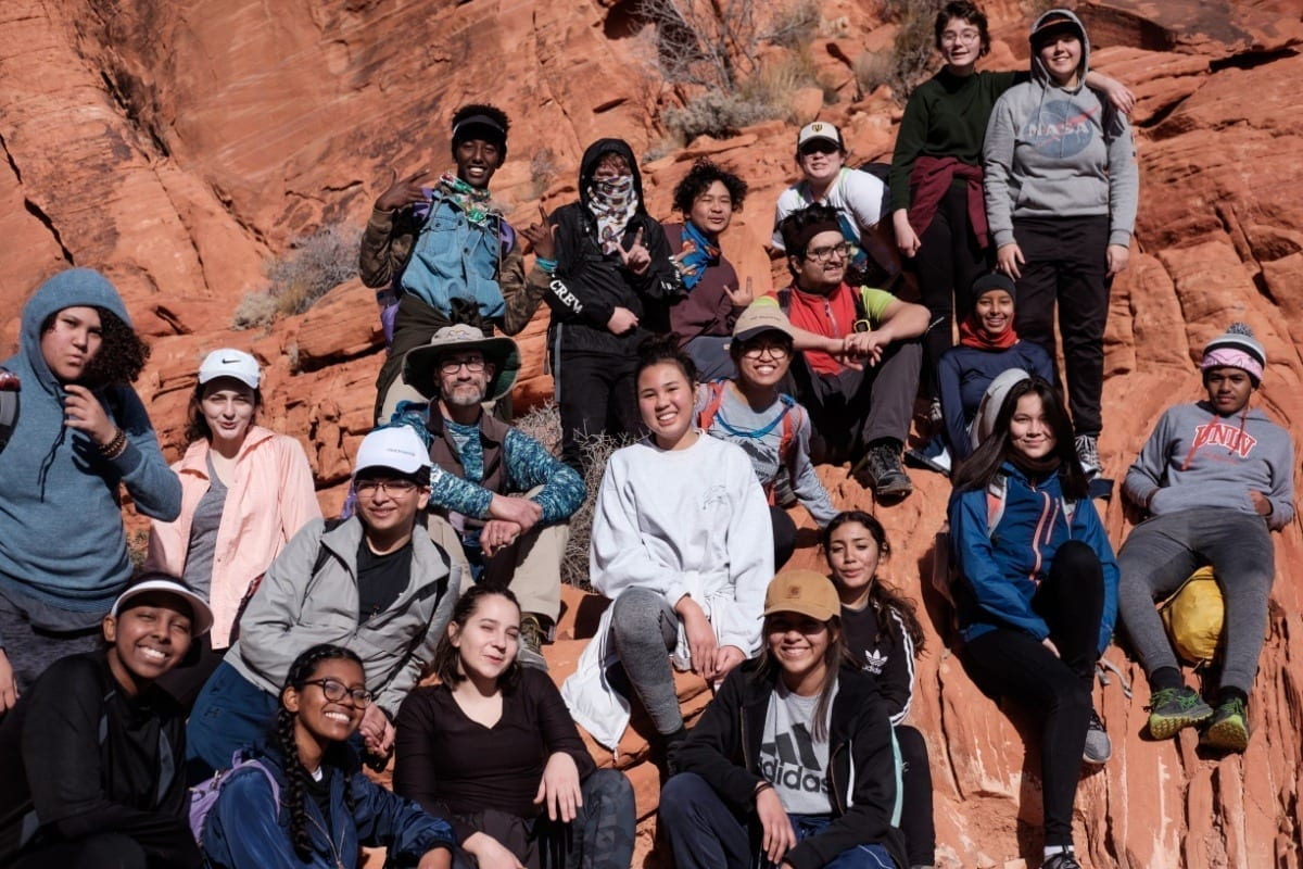 large group of teens posing for a photo on a rock wall at a national park