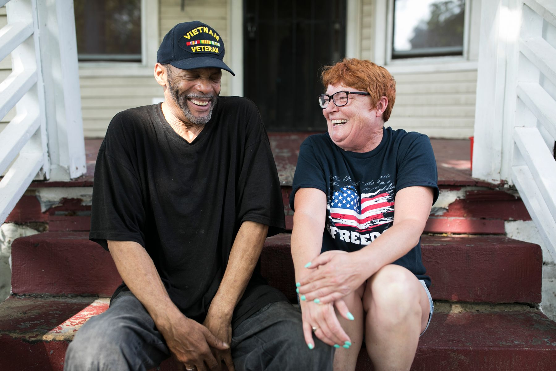 two veterans sitting on a porch laughing