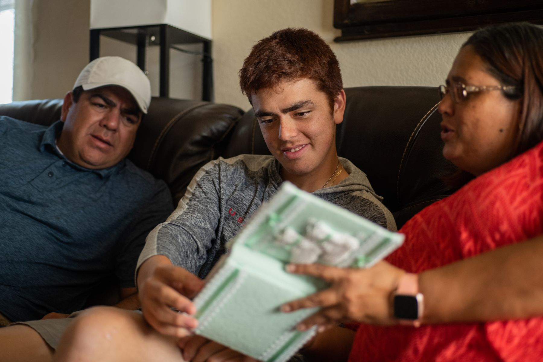 Young man and his parents sitting on a couch looking at a book