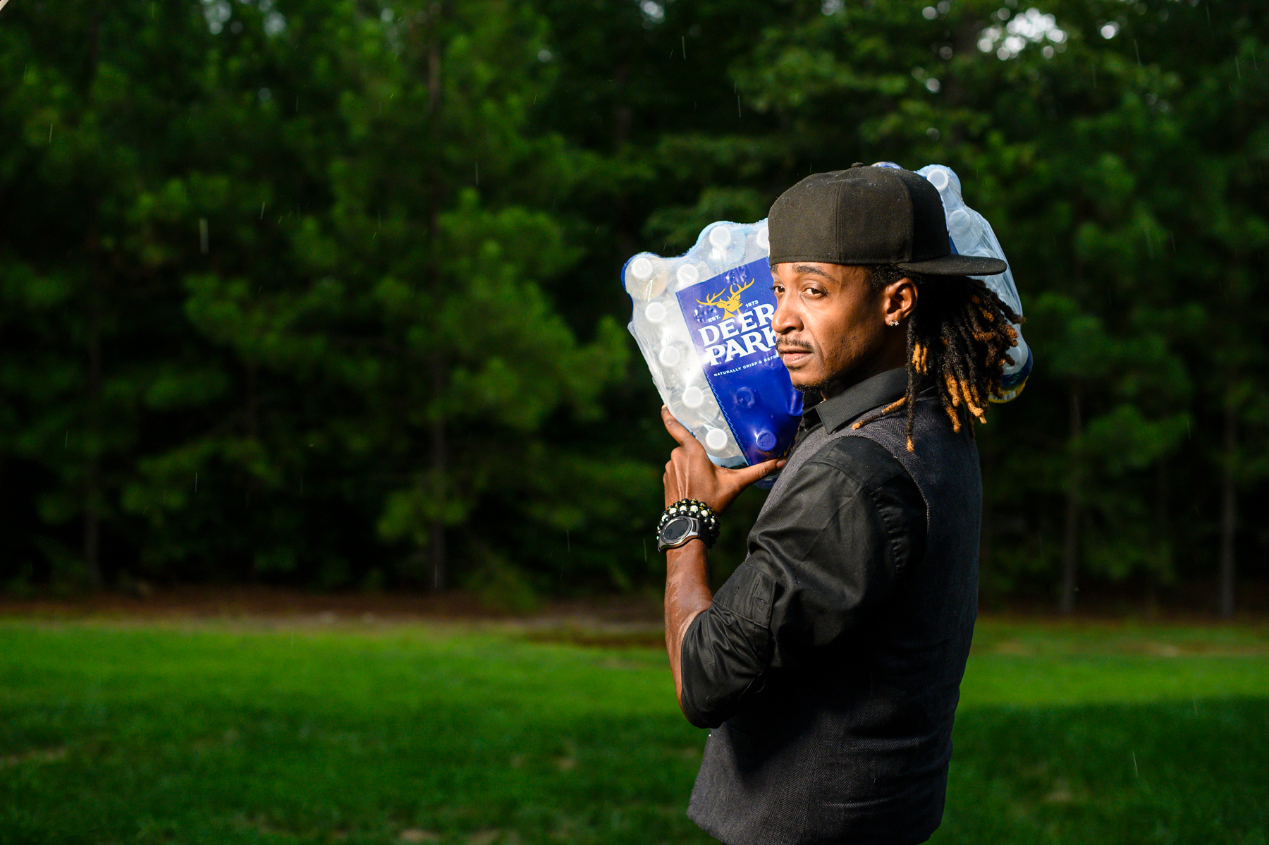 man on grassy field carrying pack of water bottles over his shoulder