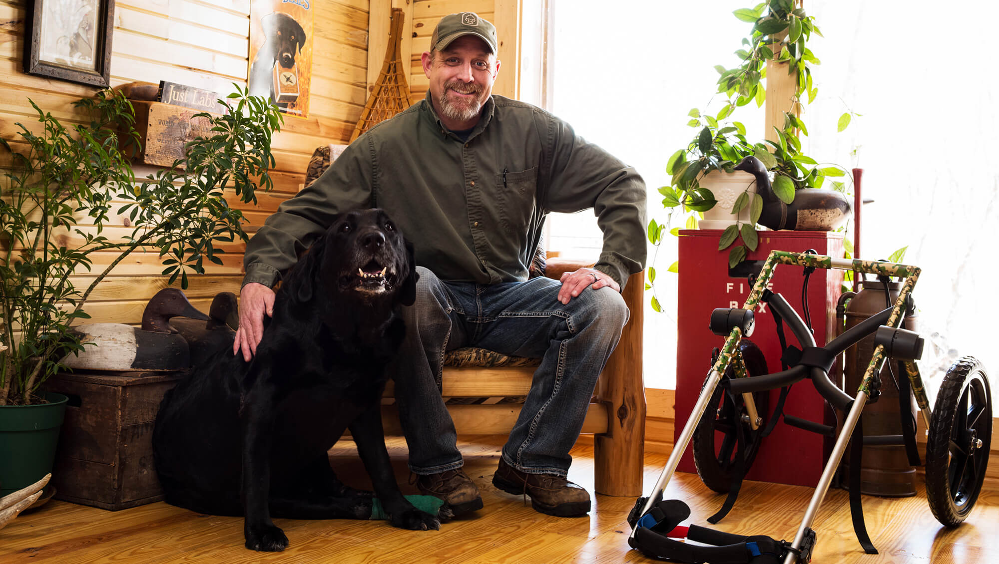 man with his dog smiling for the camera in their home