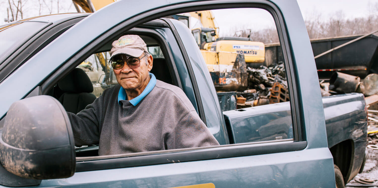 Elderly man sitting in front seat of truck with door slightly open