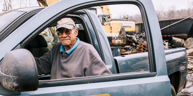 Elderly man sitting in front seat of truck with door slightly open
