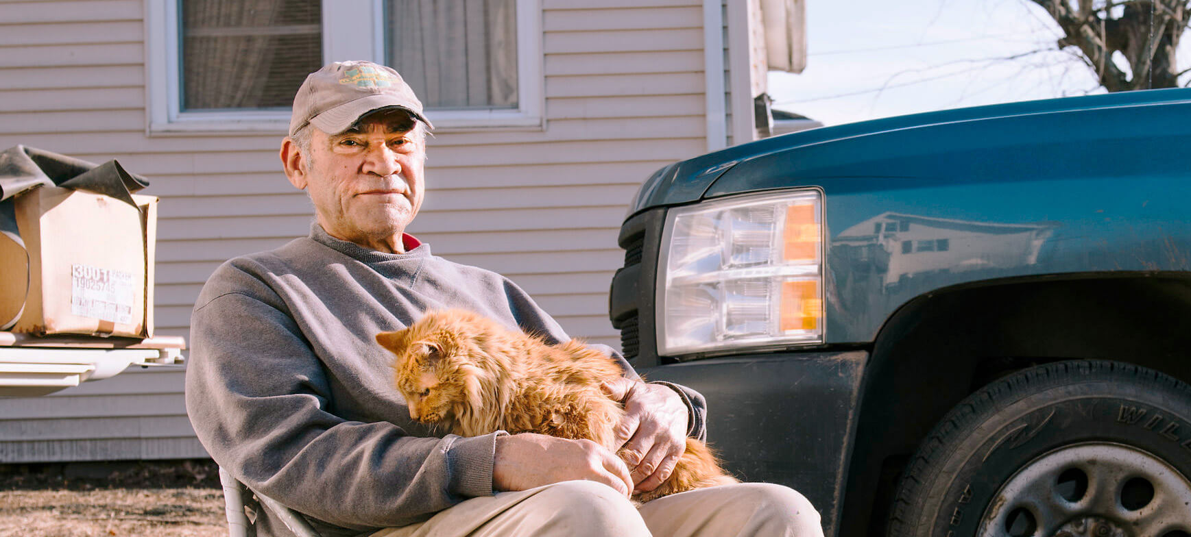 Elderly man sitting outside with his cat on his lap