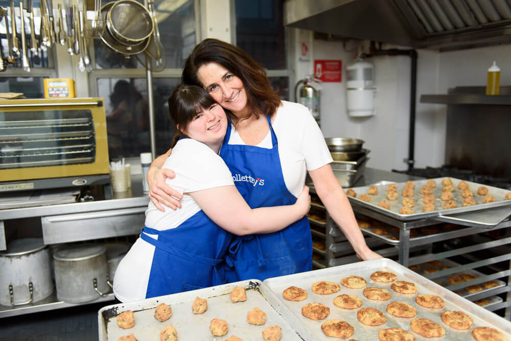 Two women hugging in front of cookie trays