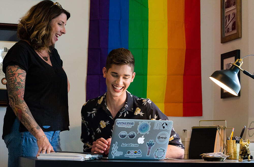 young man on laptop talking to woman standing next to him with rainbow flag behind them
