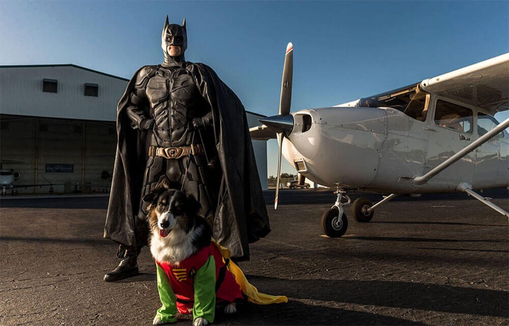 Man and dog dressed as Batman and Robin with a plane in the background