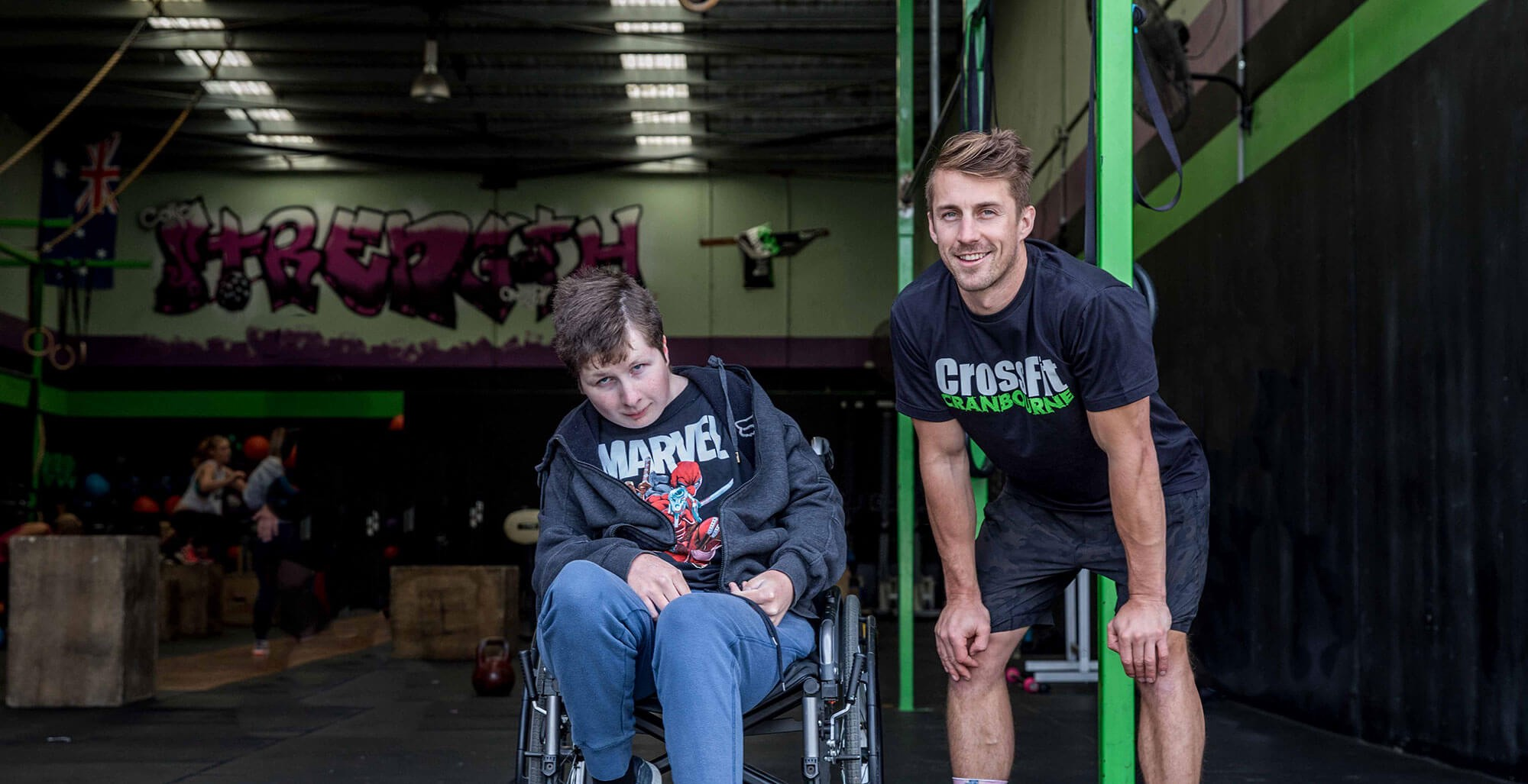 Young boy in a wheelchair with man standing in front of a gym