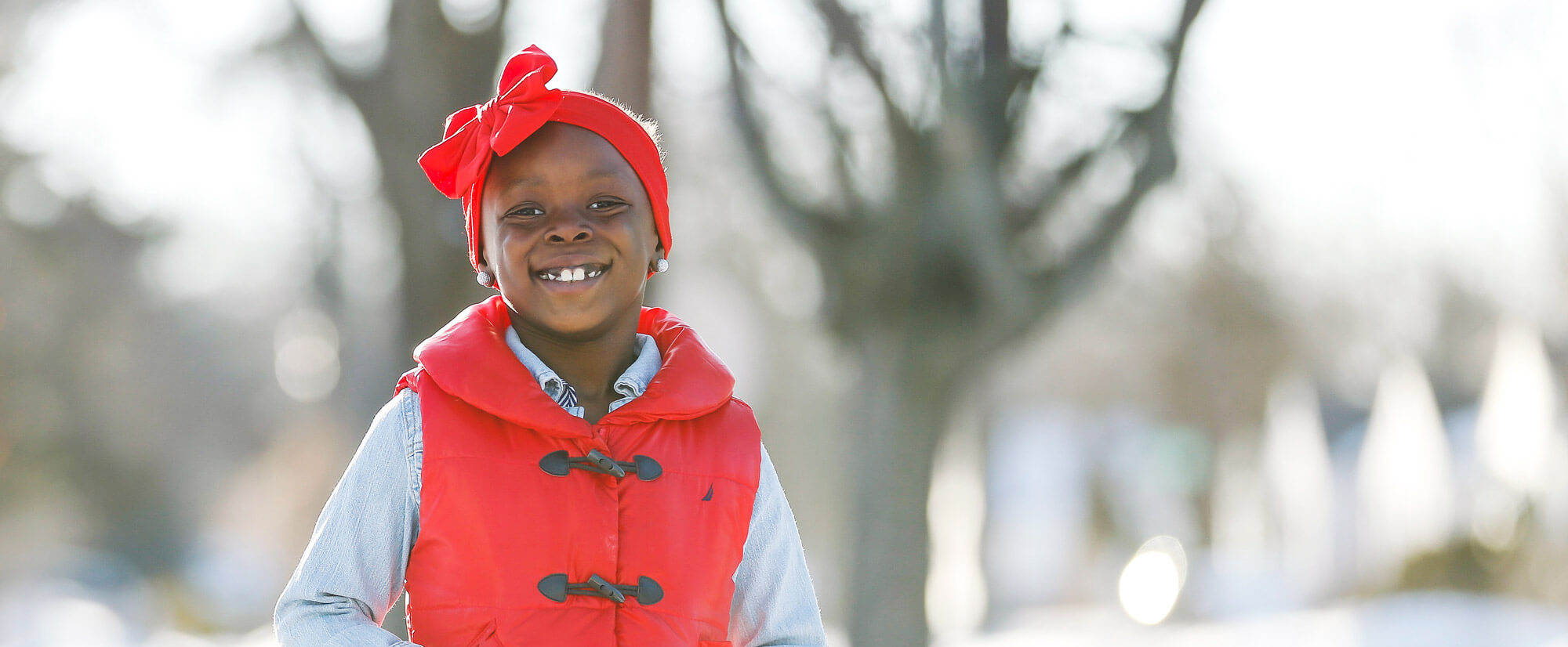 Little girl in a red vest smiling