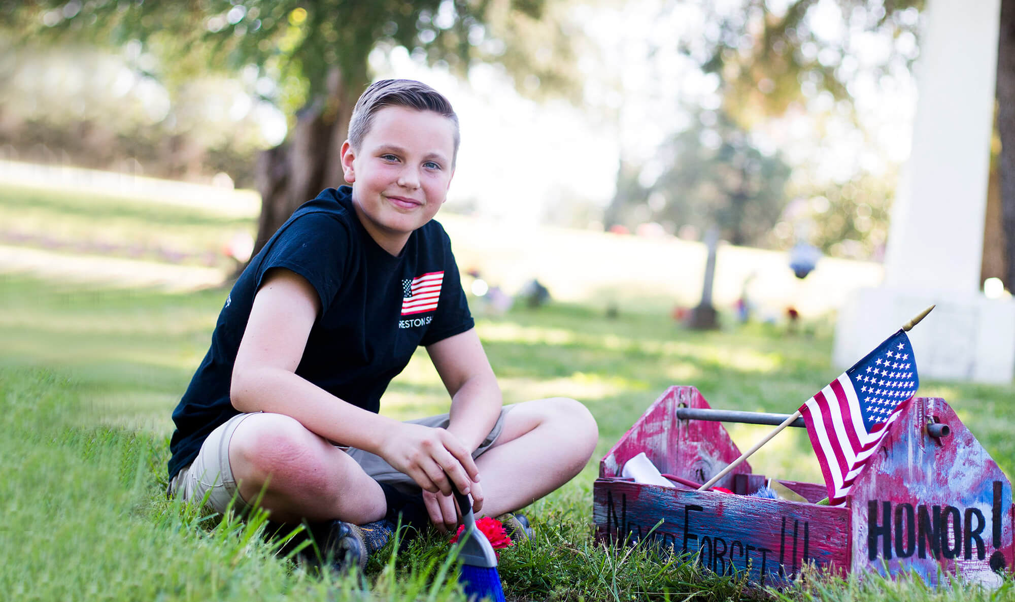 Boy smiling and sitting in the grass