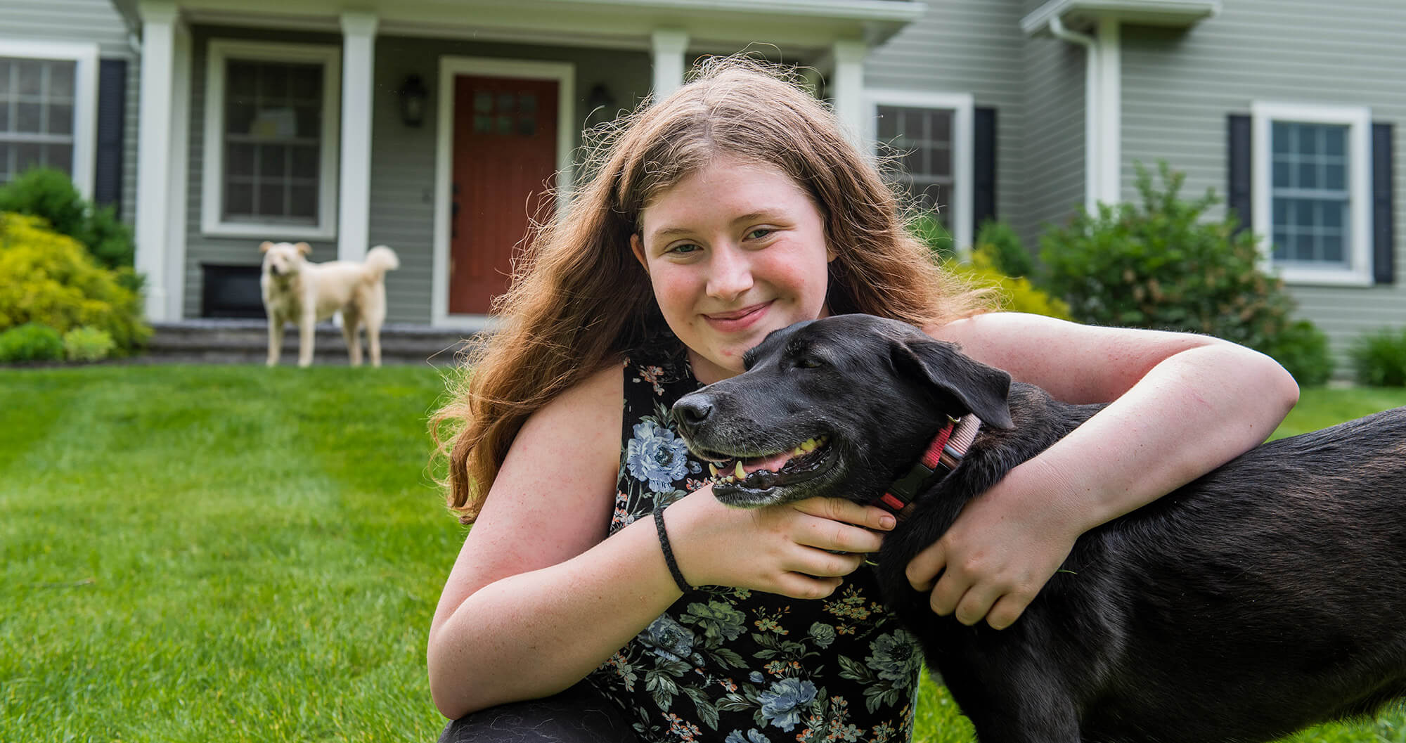 Girl smiling and holding a black dog