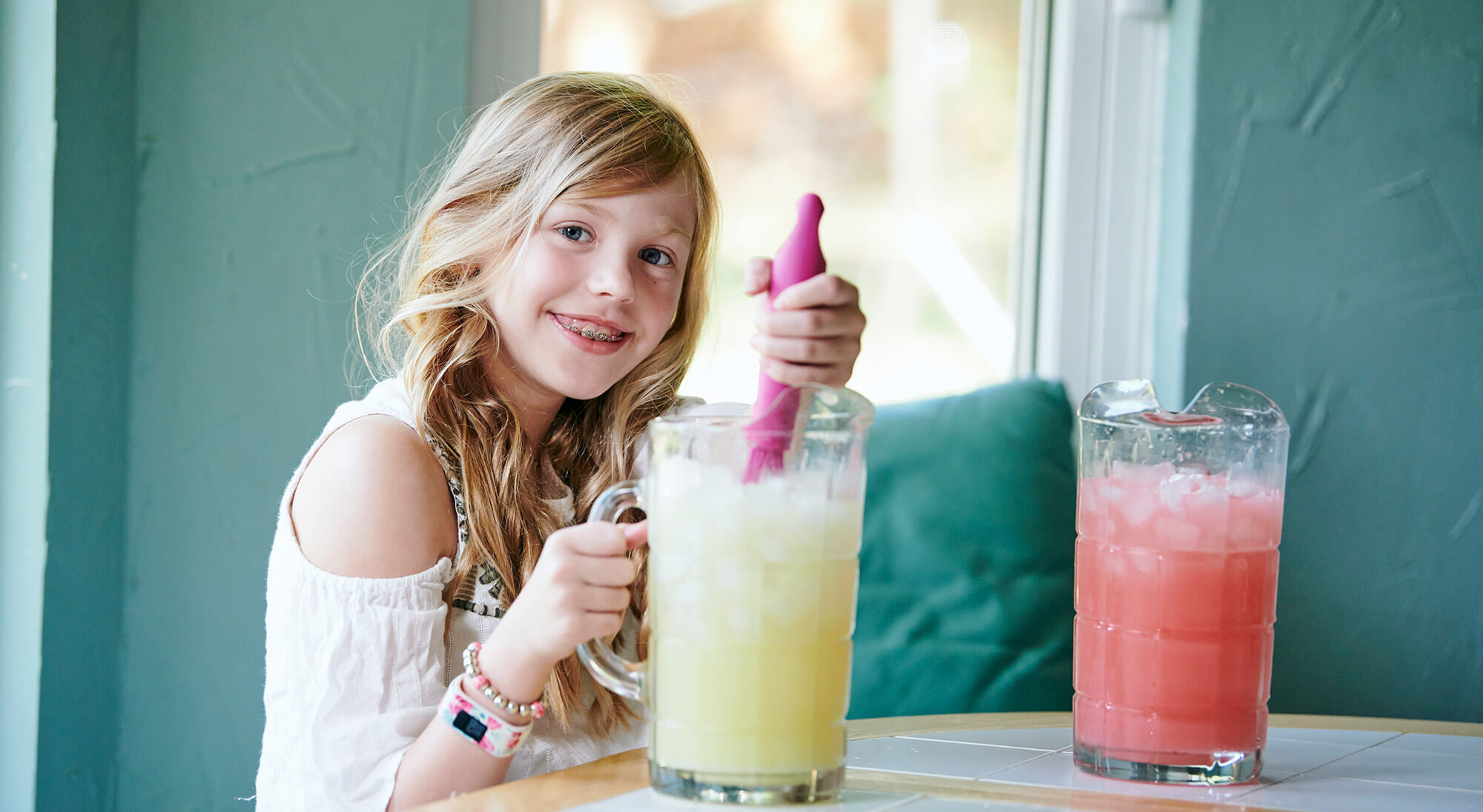 Young girl smiling while making lemonade
