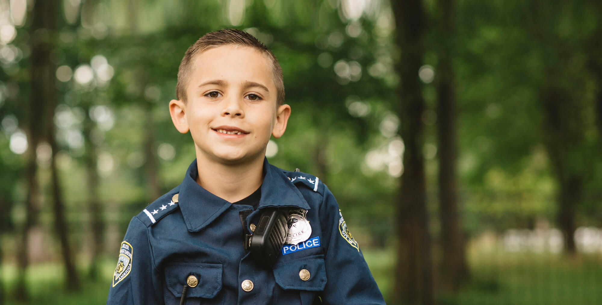 Little boy wearing a police costume and smiling