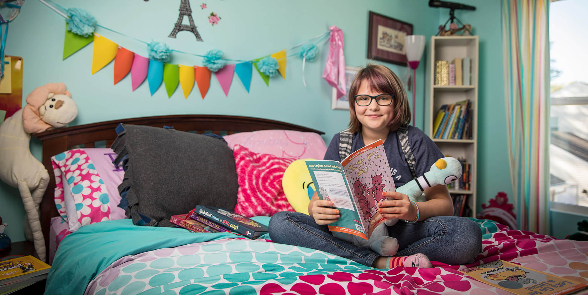 Girl sitting on a bed smiling and holding a book