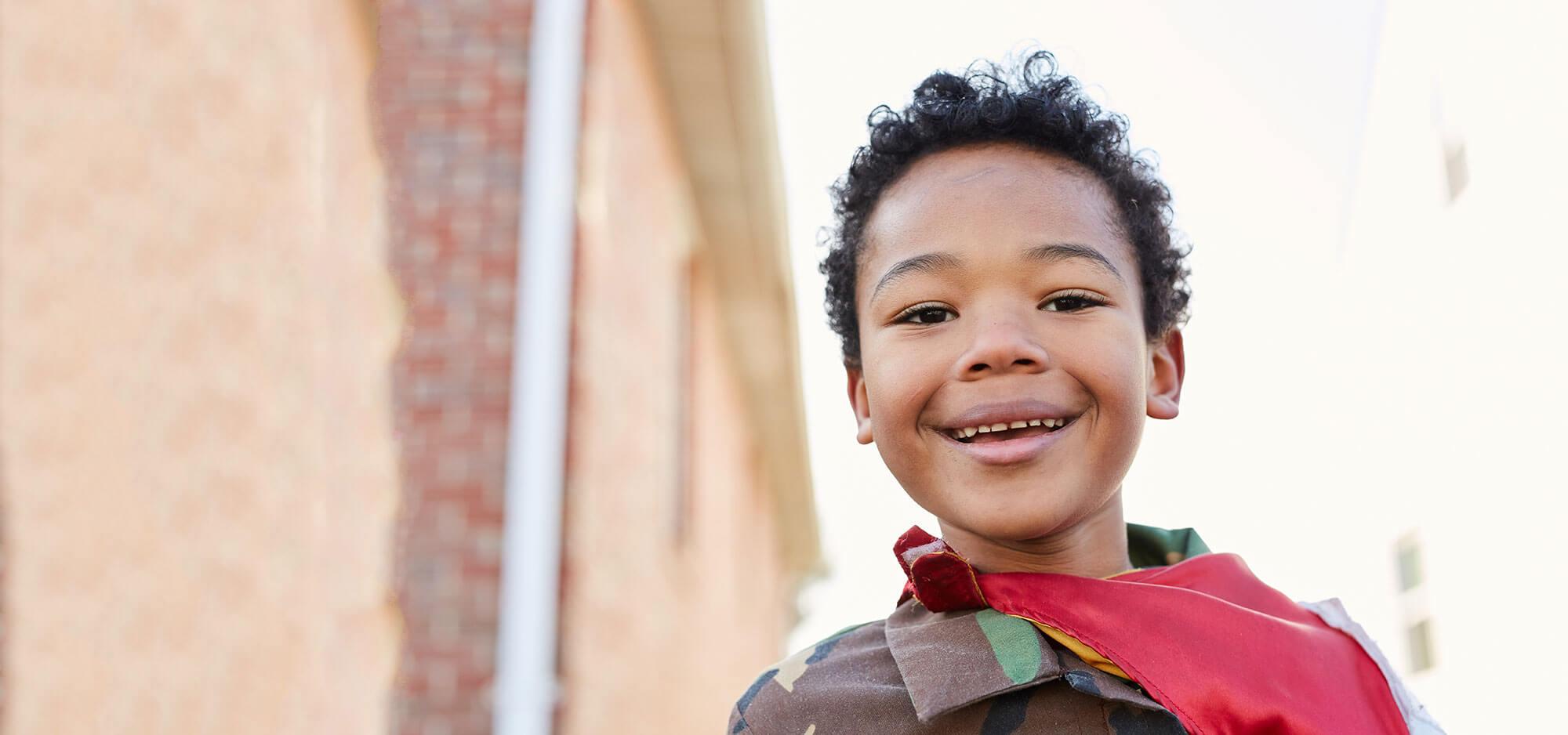 Little boy in cape smiling