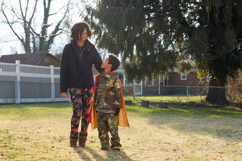 young boy wearing a cape standing and smiling next to his mom